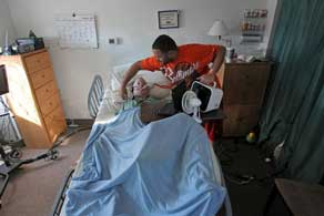 Person in hospital bed receiving care from caregiver